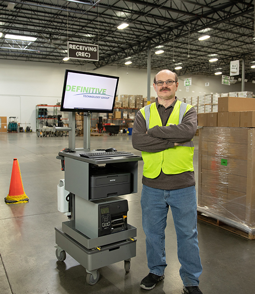 warehouse worker standing next to monitor workstation in warehouse